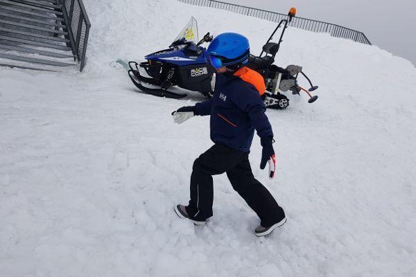 jongen loopt met snowboots in sneeuw