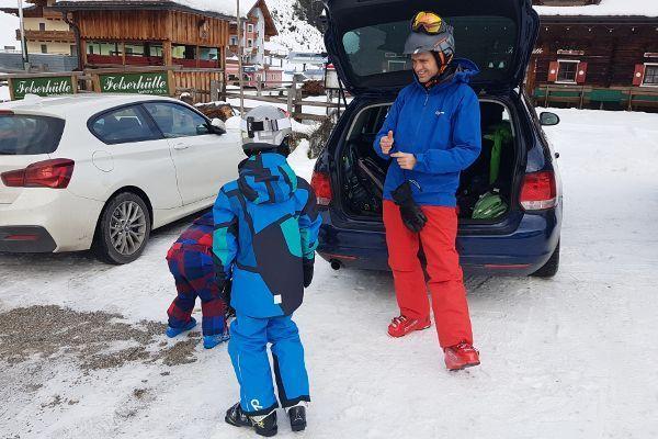 gezin wisselt van snowboots naar skischoenen bij de auto