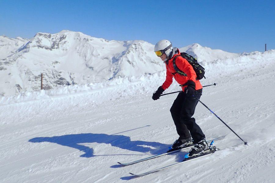 skibroek ski in de zon witte helm zwarte broek