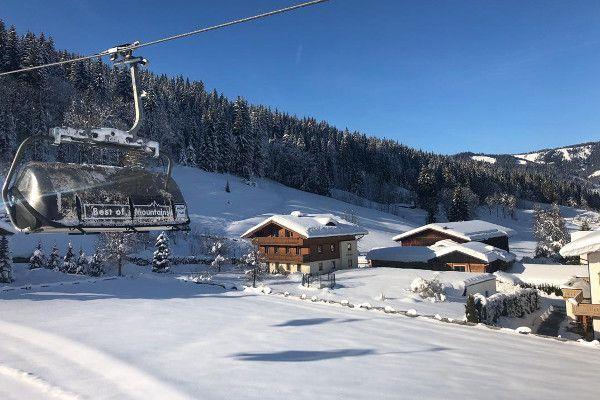 Winterbeelden: zon in Flachau met skilift